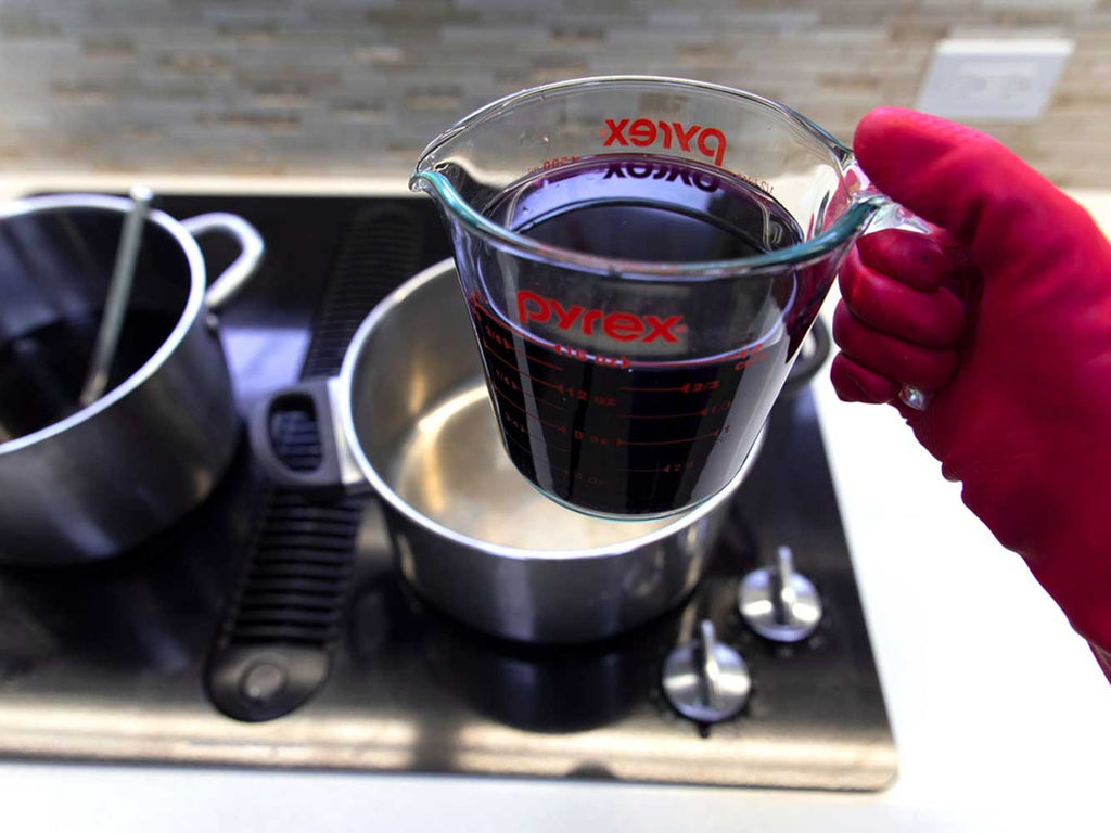 A red-gloved hand holding a measuring cup filled with dark purple dye water. In the background there are two pots sitting on a stovetop.