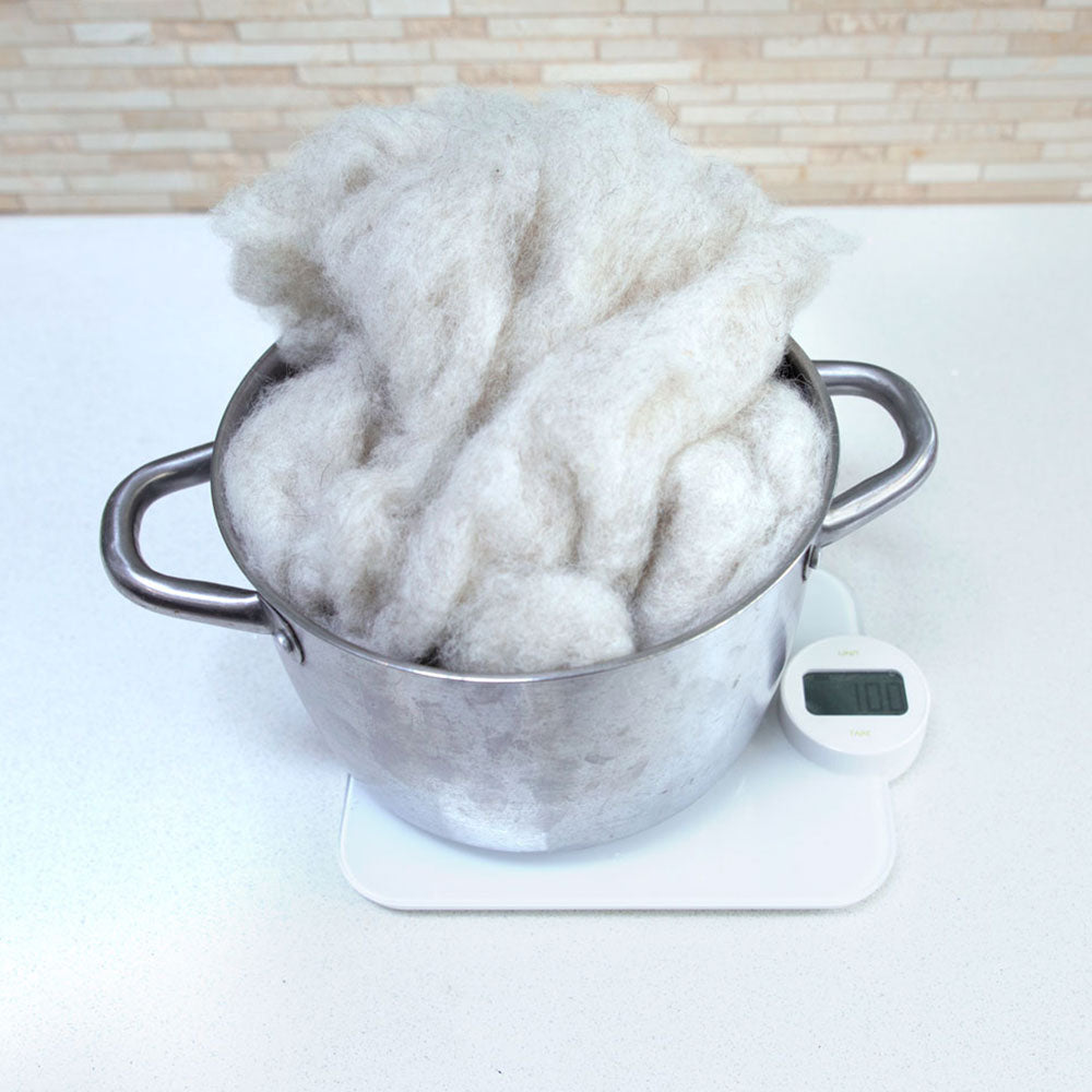 A stainless steel pot filled sitting on a kitchen scale with fluffy carded wool inside the pot