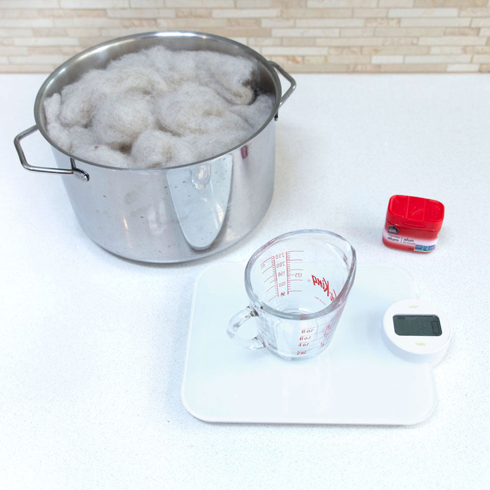 A picture with a measuring cup on a kitchen scale. A spice container of alum and a pot with carded wool is in the background