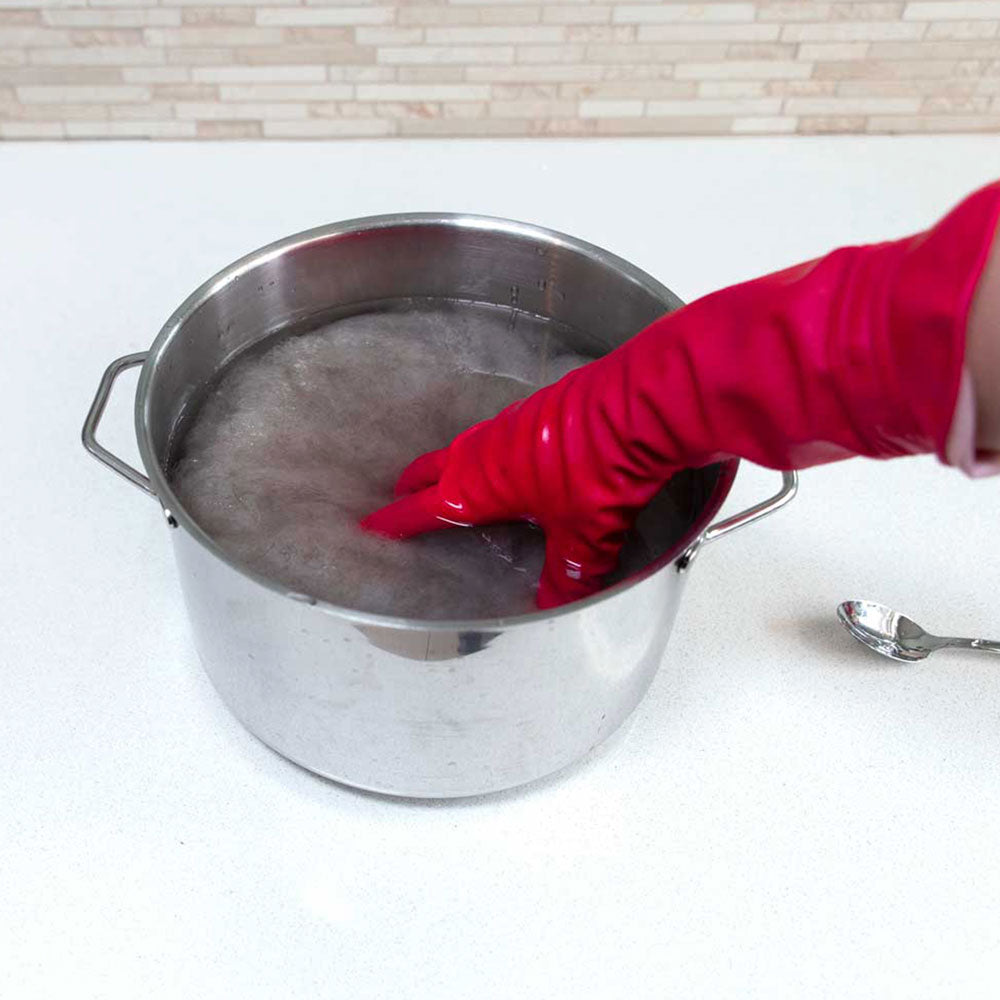 Submerging carded wool into a stainless steel pot filled with a warm water Alum solution.