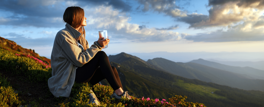 woman sitting on grassy hill holding stainless steel insulated tumbler