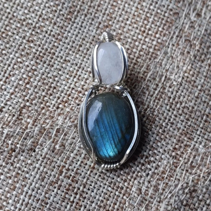 "a beautiful and petite sterling silver wire wrapped pendant featuring labradorite and rainbow moonstone, both with very striking blue fire flash iridescence. comes with an 18"" sterling silver chain."