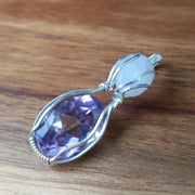 "rainbow moonstone compliments this stunning faceted amethyst, hand wrapped in sterling silver wire and sent to you with an 18"" sterling silver chain."