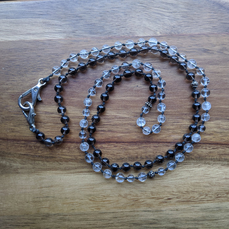 This full 108 bead mala is half clear quartz and half smokey quartz with a sterling silver marker at the 54 bead mark.