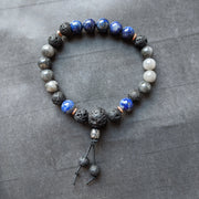 vibrant blue lapis lazuli paired with grey hawk eye, copper spacers and essential oil diffusing lava beads.