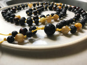 108 bead mala made with black lava stone for essential oil difusion highlighted with gold tiger eye and red tigereye natural gemstones