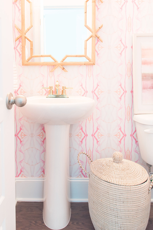 wallpaper installation, rattan mirror bathroom, pink powder room, pink wallpaper, pink painted wallpaper, artist wallpaper, pink powder room