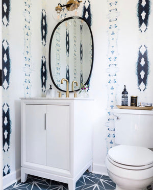 bathroom cement tiles, blue encaustic tiles, cement tile floor bathroom, navy white bathroom, navy white powder room, navy white wallpaper bath, oval vanity mirror charlotte interior designer