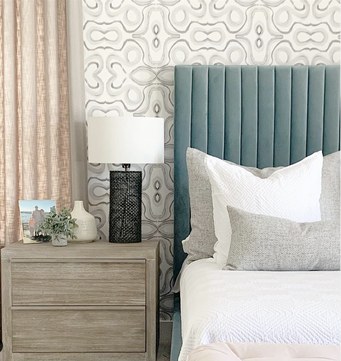 wallpaper accent wall behind bed, aqua blue velvet headboard, beige trimmed drapes, arizona bedroom design