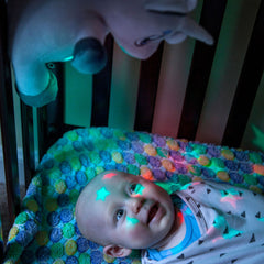 baby in crib looking up at sound soother