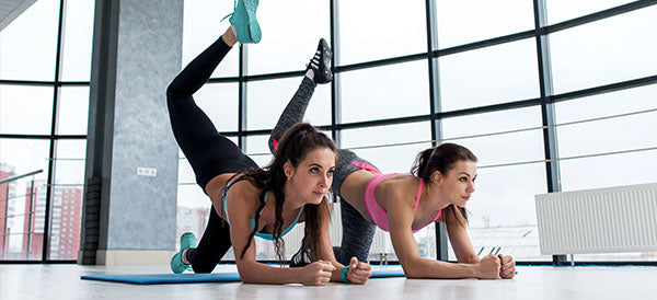 Two sportive girlfriends doing butt toning exercise