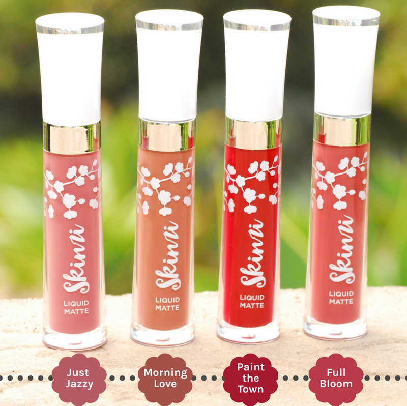 Image of 4 Skinzi Liquid Mattes on top of a stone wall overlooking a green grassy field, with Just Jazzy showing first followed by Morning Love, Paint The Town and Full Bloom. The labels are also specified under each lipstick shade.