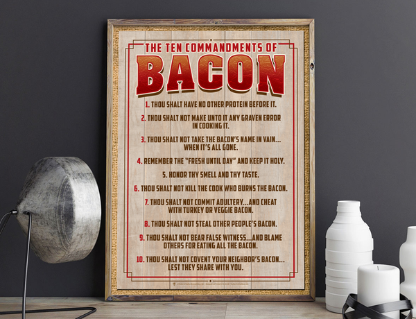 Ten commandments of bacon, funny bacon poster print, canvas print, shown displayed on kitchen counter, grey wall in backbround, silver lamp.