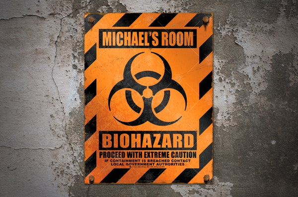 Orange and black biohazard caution sign print, displayed on a distressed wall background.