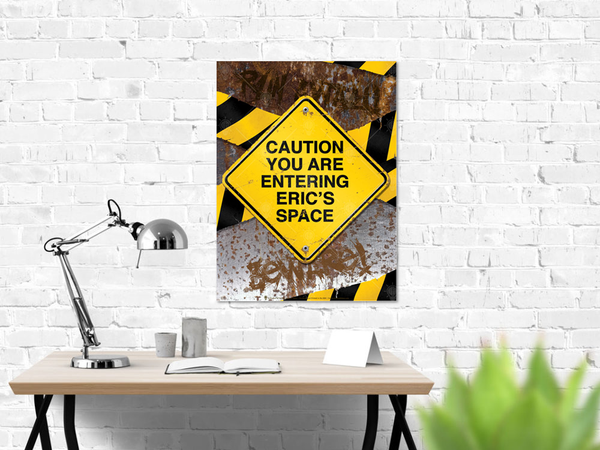 Caution you are entering my space, distressed caution sign print, shown displayed on white brick wall, work desk and silver desk lamp, green plant, desk materials.