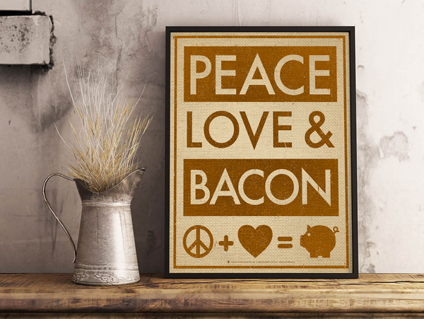 Peace, love and bacon, poster print, canvas print, shown displayed in a dark frame, grey plaster wall, silver pitcher, dried grass, wood table top.