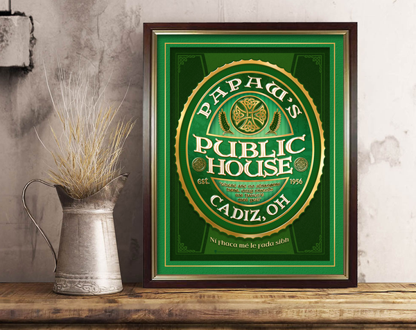 The public house, personalized Irish pub sign, poster print, canvas print, framed print, displayed with green mats, brown frame, wooden counter top, metal pitcher, dried grass.