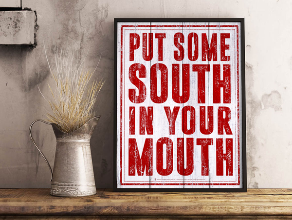 Put some South in your mouth, old country poster print, canvas print, displayed in a black wood frame, grey plaster wall, silver pitcher, dried grass, wood table top.