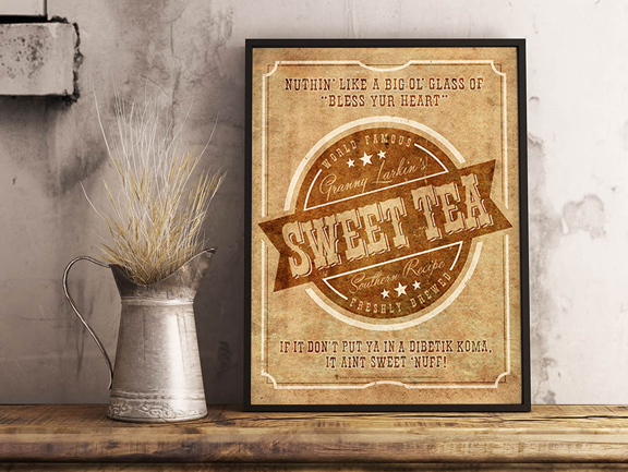 Your brand sweet tea, personalized poster print, canvas print, displayed in a dark brown frame, grey rustic wall, tin pitcher, dried grass, wood table top.