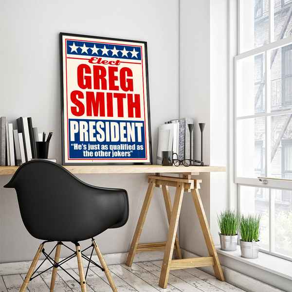 The run, personalized faux political campaign poster, displayed in a wood frame, leaning on white wall, work room, books, wood table, black chair, large window, green plant.