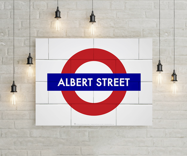 English underground symbol, your name for the street name, shown mounted to white brick wall, hanging lights.
