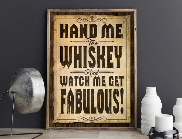 Hand me the whiskey and watch me get fabulous, poster print, canvas print, shown displayed in a barn wood frame, against a deep grey wall, silver lamp, bottles.