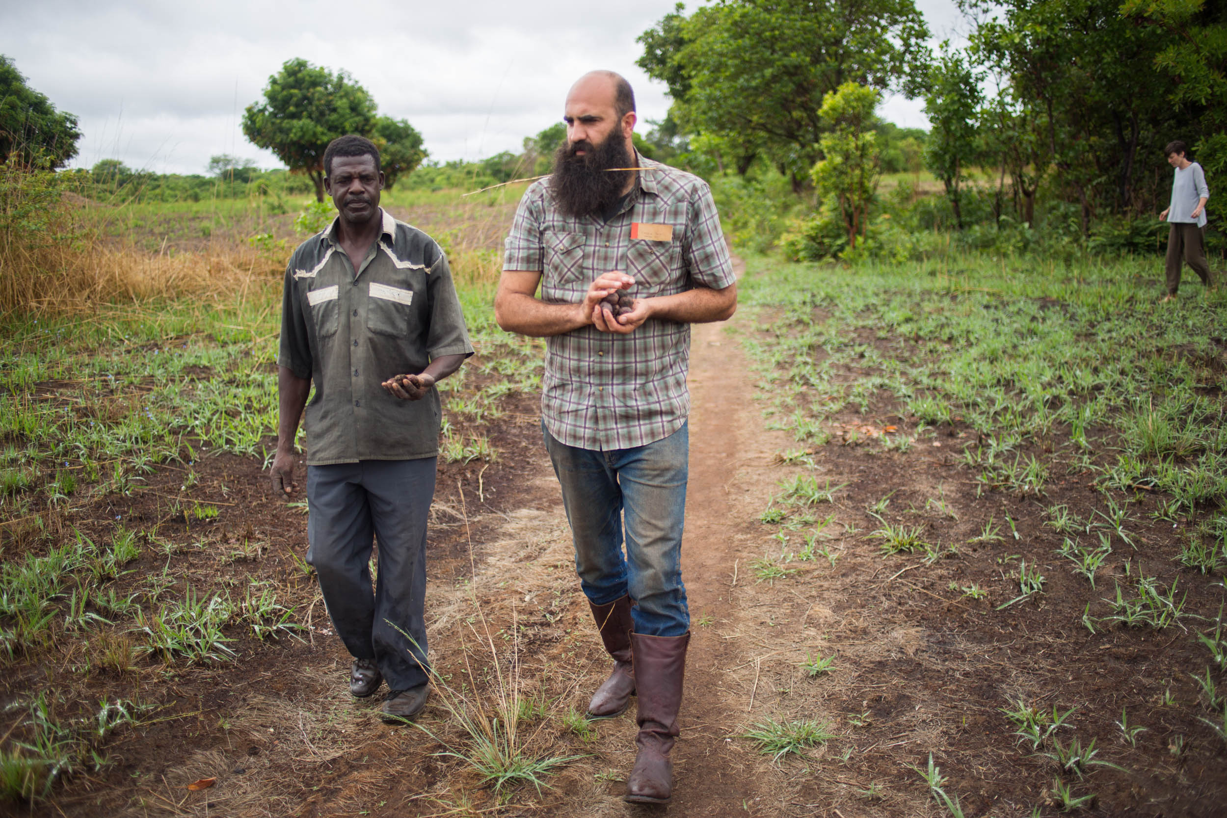 Zambeezi Founder André walking and discussing farming with Zambian Beekeeper and Arborist