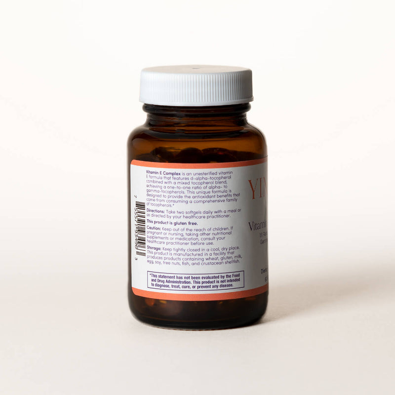 List of ingredients for Vitamin E Complex tablets on the back of a clear brown bottle.
