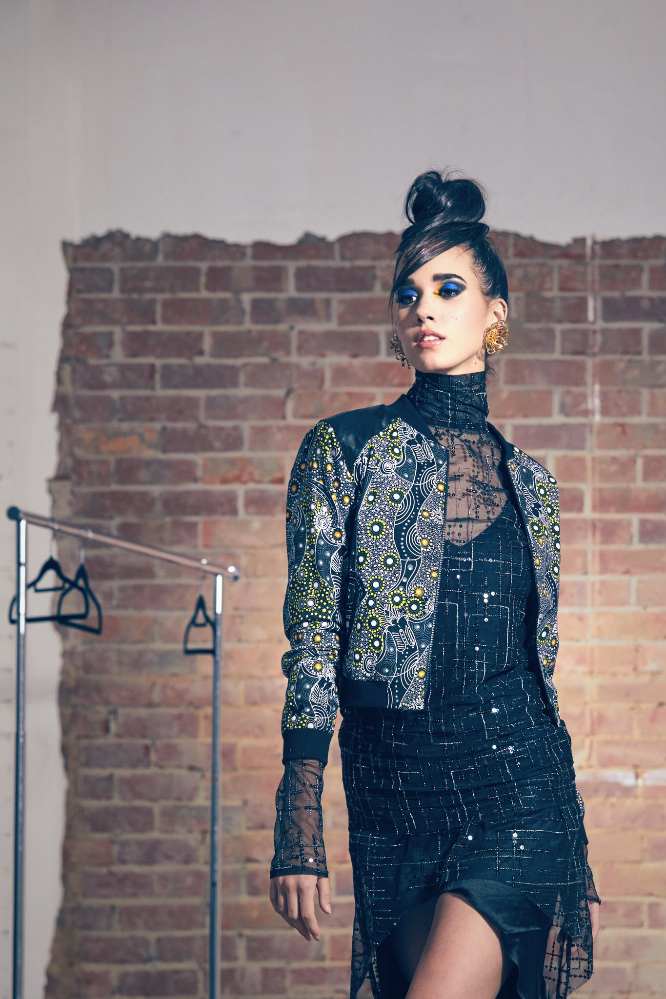 Model wears sequin and silk dress with Dancing Spirit bomber jacket