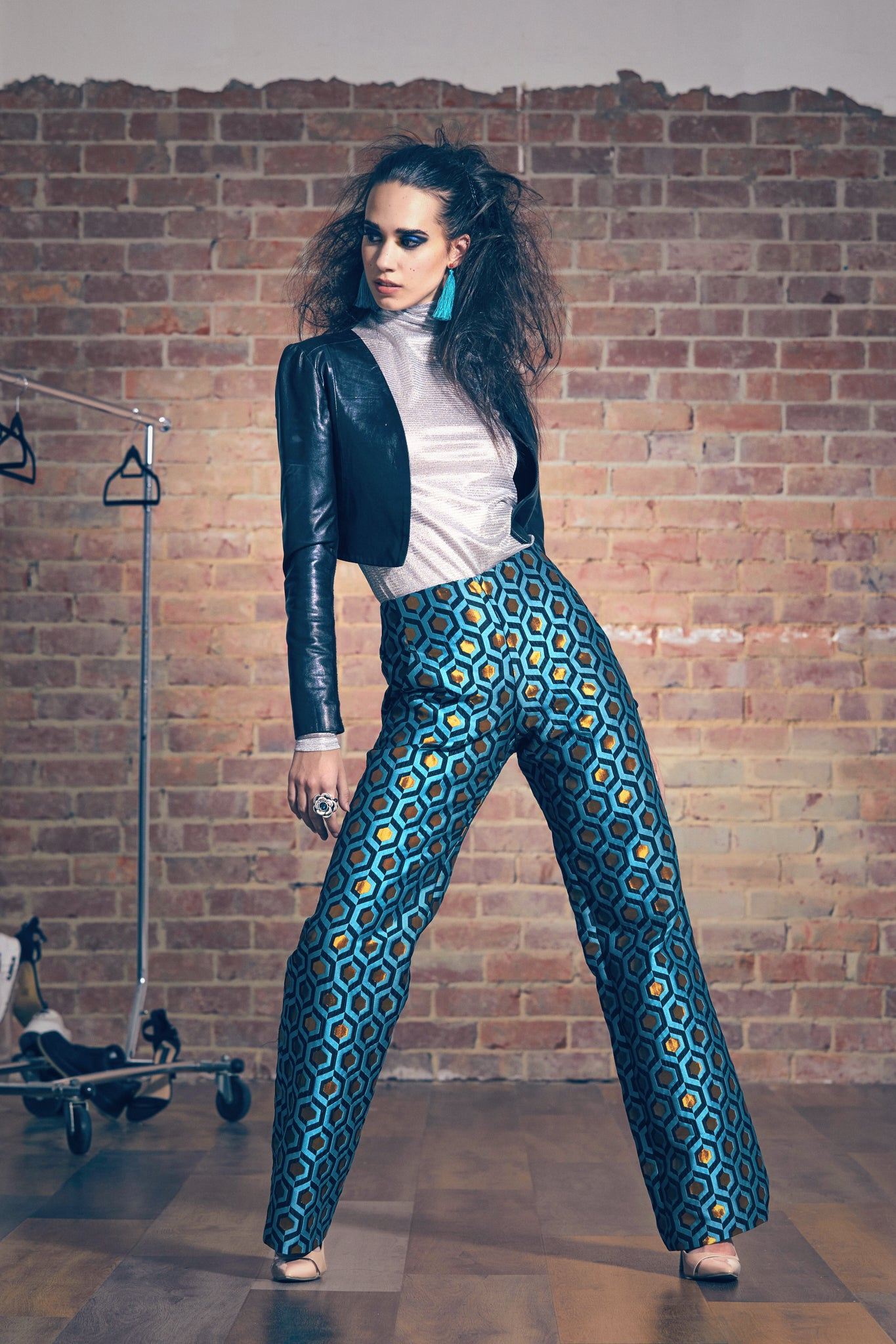 Model wears brocade wide leg pants with silver turtleneck and leather crop jacket