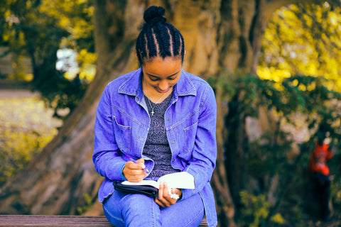 Photo by Gift Habeshaw on Unsplash Black woman with braided hair reading a book outside