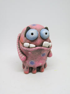 Pink 9 legged monster with extra big teeth and eyes