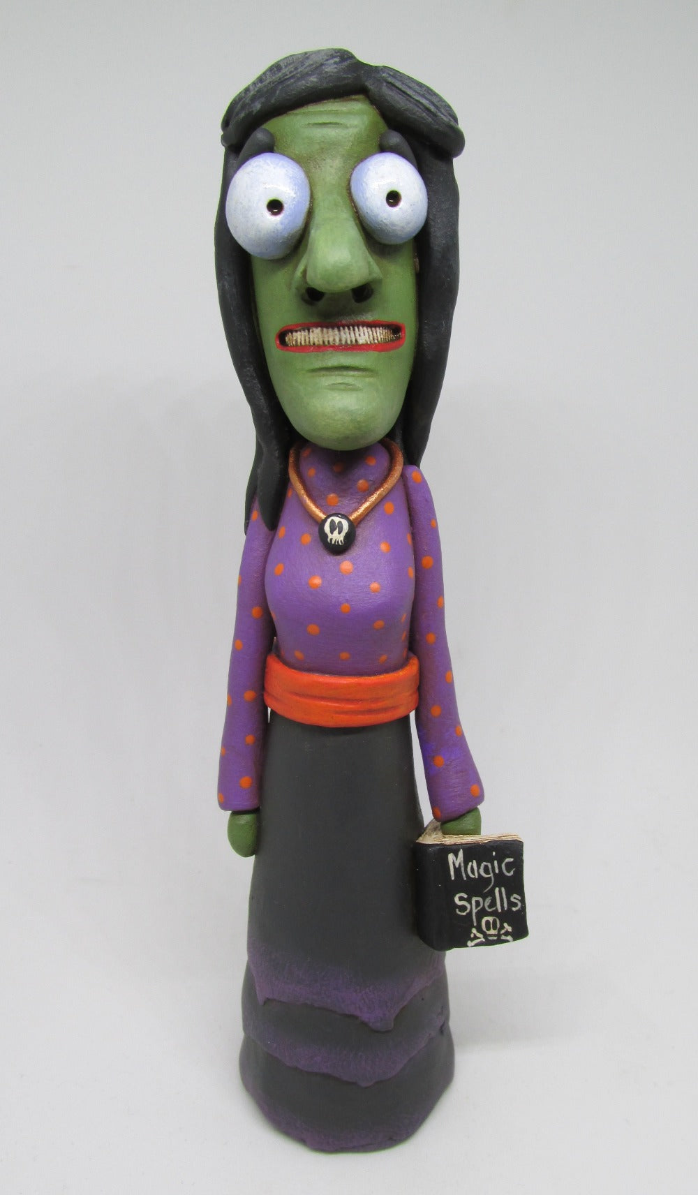 Halloween folk art witch with book of spells