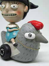 Girl with big head and pair of goggles riding a chicken