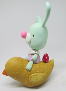Easter mint colored bunny rabbit riding a spring chick