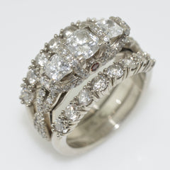 14K White 3 square stone diamond ring with small diamond accent stones along band and claws of 3 centre stones. It has diamond wedding bands on either side of the 3 stone engagement ring