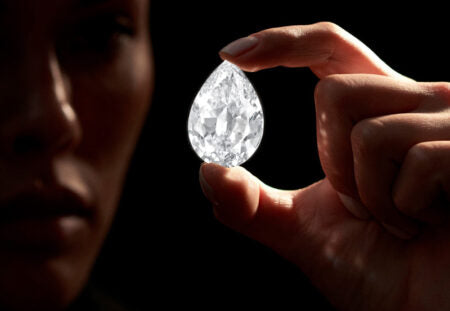 A Man looking at very large pear shaped diamond, holding between his thumb and fore finger