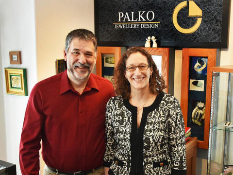 Chris and Carol Palko, happy husband and wife team of Palko Jewellery Design.  Smiling and standing in their showroom, arm in arm.