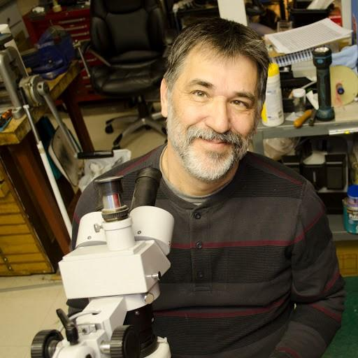 A smiling bearded man, Chris Palko, sitting facing us from behind his microscope at his workbench.
