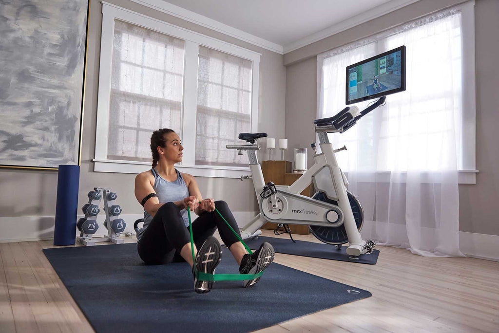 MYX member doing stretch band exercise on the mat while watching MYX coach on the MYX bike tablet