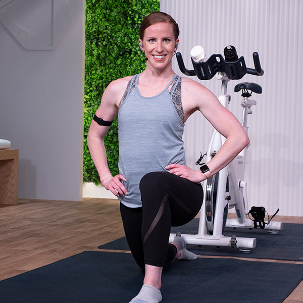 Female fitness instructor in a lunge with indoor bike
