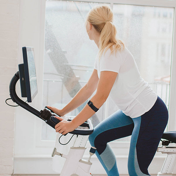 Woman working out on stationary bike looking outside