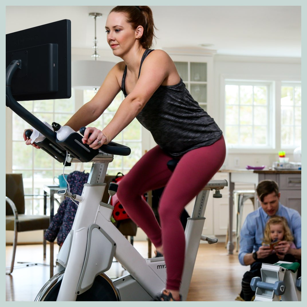 MYX Member working out on her bike with her husband and daughter playing in the background