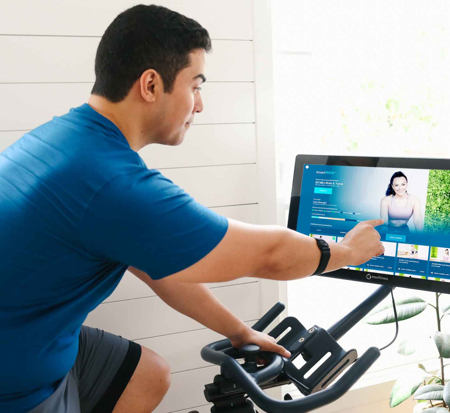 Guy on his MYXfitness bike selecting a workout on the tablet