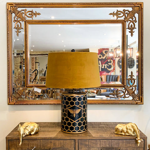 Bee lamp and peering animal accent pieces in front of a feature mirror.
