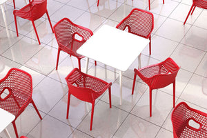 Red chairs around white table. This image represents our commercial grade furniture