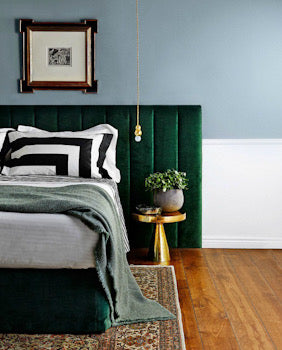 Picture showing a fluted custom made headboard in emerald green velvet.
