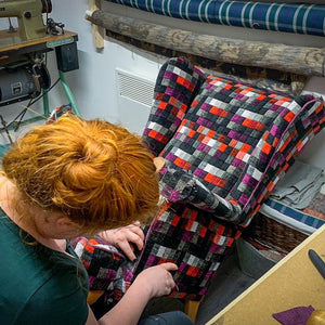 Vicky from auburn fox upholstering a wing back chair in the upholstery studio using a very colourful squared patterned fabric