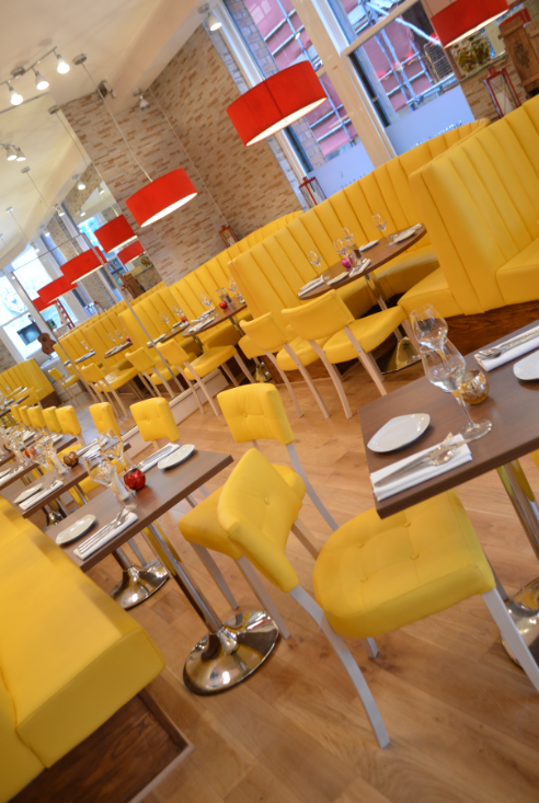Yellow booths and seats with wooden and metal tables in a restaurant, showing our contract furniture