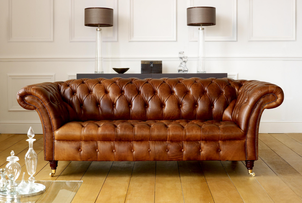 Tan leather chesterfield with metal casters. Contract sofas made to order for commercial settings
